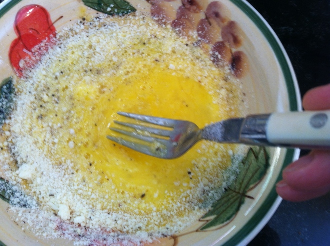 whisking egg with parmigiano